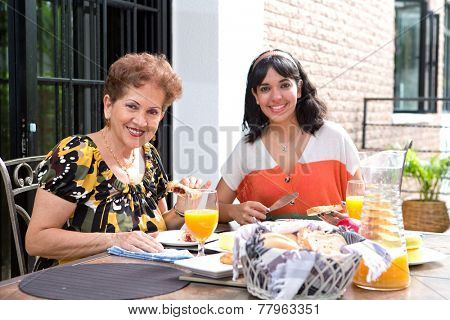 A senior hispanic woman having breakfast outdoors with a daughter. Outdoor dining in summer. Focus on senior woman.