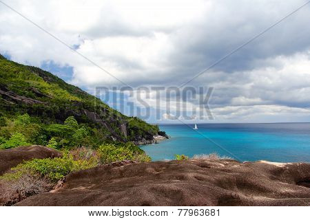 Rocky Landscape In The Seychelles With Sailboat In The Distance