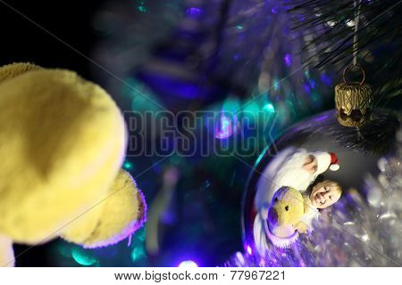 Santa Claus with gifts and funny boy in a New Year's ball reflection