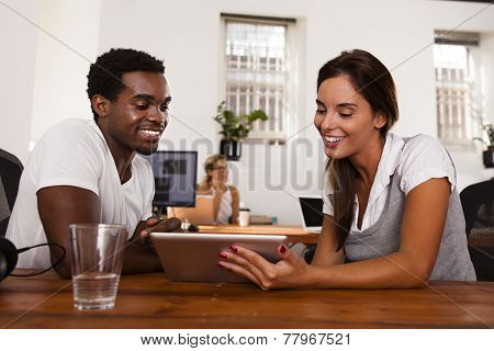 Startup Entrepreneurs Discussing A Tablet Computer