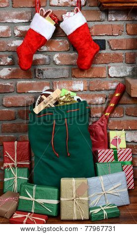 Santa Claus' bag leaning on the bricks of a hearth. The bag is stuffed with toys and surrounded by wrapped presents. Two stockings hang above. Vertical format.