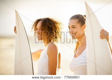 Two Girl Surfers At Sunset