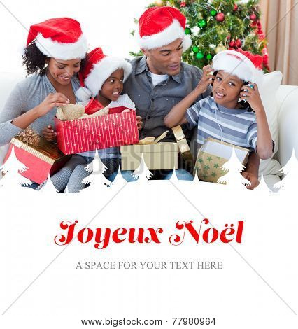 Happy family playing with Christmas presents against joyeux noel