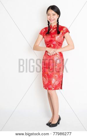 Portrait of full length Asian Chinese female, in traditional red qipao dress standing on plain background.