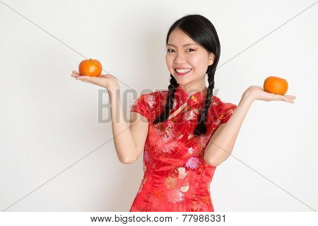 Portrait of Asian Chinese girl hands holding tangerine orange, in traditional red qipao standing on plain background.
