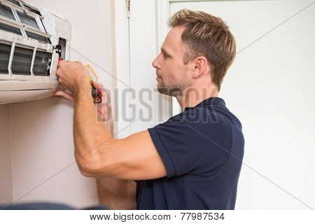 Focused handyman testing air conditioning on the wall