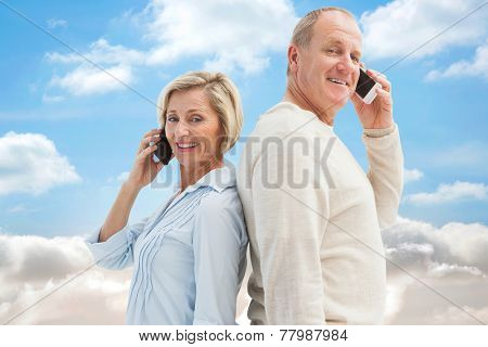 Happy mature couple talking on their phones against cloudy sky