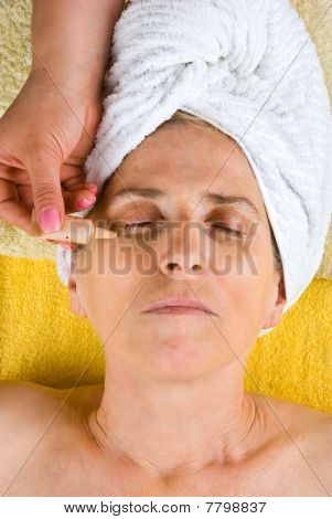 Beautician Applying Serum To Senior Face