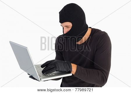 Focused burglar standing holding laptop on white background