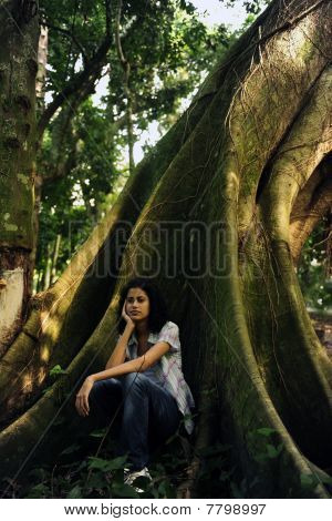 Happy Woman Sitting In The Shadow Of A Tree