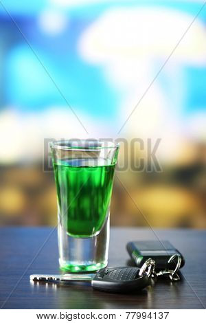 Glass of alcoholic drink and car key, on wooden table, on light background