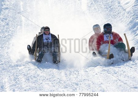 Men ride traditional horn-sledge in Grindelwald, Switzerland.