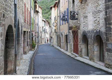 People at the calm narrow street of the medieval town, Villefranche de Conflent, France.