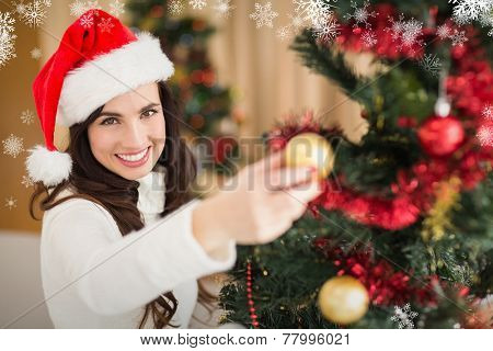 Festive brunette decorating a christmas tree against snowflakes