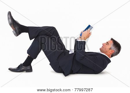 Relaxed businessman lying and reading book on white background
