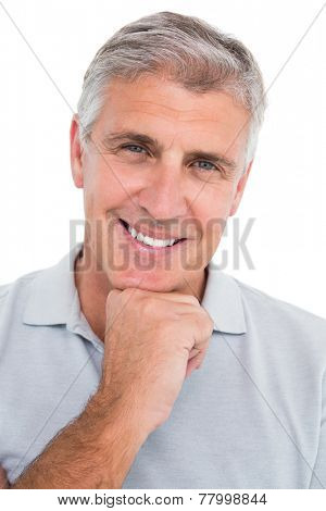 Casual man smiling with hand on chin on white background