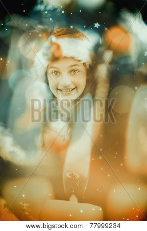 Festive litte girl decorating christmas tree against candle burning against festive background