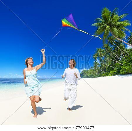 Couple flying a kite on the beach.