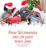 pic of weihnachten  - Happy family playing with Christmas presents against frohe weihnachten message - JPG