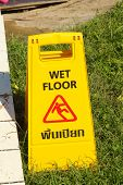 picture of slip hazard  - Yellow sign warning for wet floor at the park - JPG