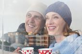 pic of glass-wool  - Happy couple in warm clothing holding mugs seen through glass window - JPG