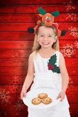 picture of rudolph  - Festive little girl holding fresh cookies against snowflake pattern on red planks - JPG