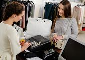 pic of showrooms  - Happy woman customer paying with credit card in fashion showroom - JPG