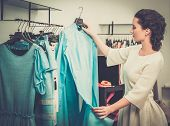 stock photo of racks  - Young woman choosing clothes on a rack in a showroom  - JPG