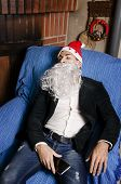 picture of hangover  - Young man with Santa Claus costume sleeping with possible hangover at sofa before christmas party - JPG