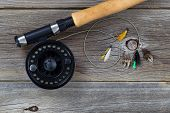 image of fly rod  - Close up of a fly reel with line and assorted flies and partial cork handled pole on rustic wooden boards - JPG