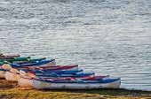 image of kayak  - Several kayaks lined up one next to the other on the river bank and ready for the adventures ahead - JPG