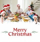 stock photo of christmas meal  - Happy family in Santa hats having Christmas meal against border - JPG