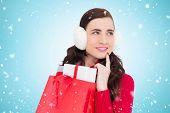 pic of muff  - Brunette with ear muffs holding shopping bag full of gifts against blue vignette - JPG