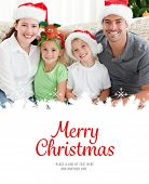 picture of christmas hat  - Portrait of a happy family with Christmas hats sitting on the sofa against merry christmas - JPG