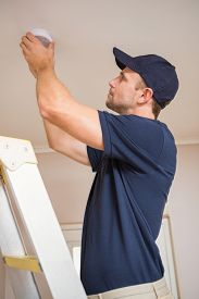 stock photo of smoke detector  - Focused handyman installing smoke detector with screwdriver on the ceiling - JPG