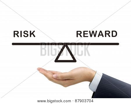 Balance Between Risk And Reward Holding By Businessman's Hand