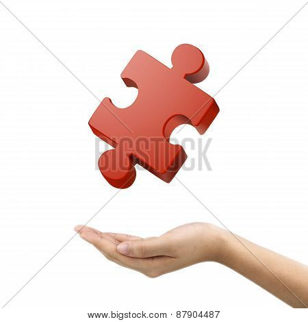 Businessman's Hand Holding Jigsaw Puzzle Piece