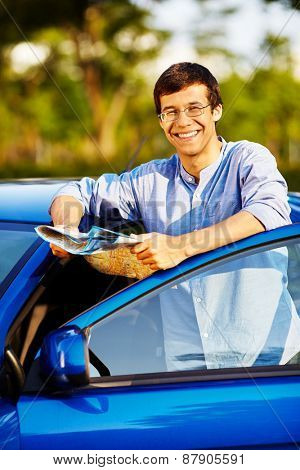 Young smiling man wearing glasses with road map leaning on blue car with open door