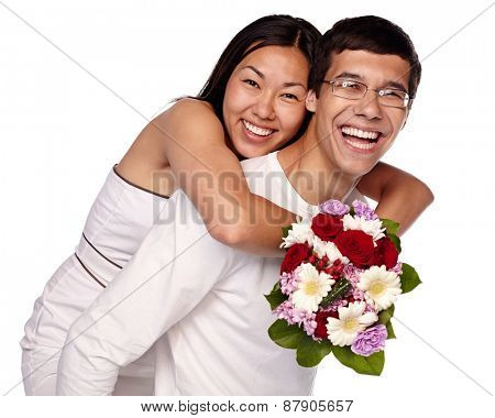 Close up portrait of young smiling woman with bouquet of flowers hugging man from behind on isolated white background