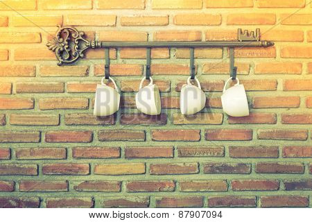 Coffee cups hanging on hooks in front of brick wall ( Filtered image processed vintage effect. )