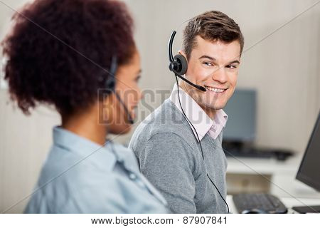 Male customer service representative talking with female colleague in office