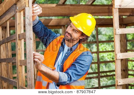 Male worker measuring timber frame with tape at construction site