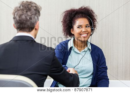 Young female customer service agent wearing headset while shaking hands with manager
