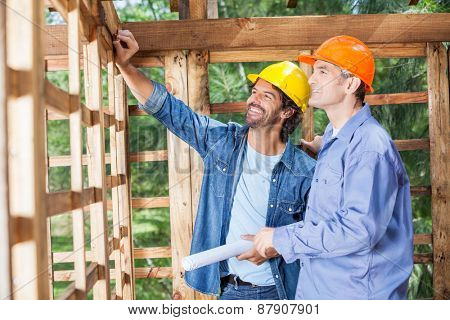Happy male architects discussing over incomplete wooden cabin at construction site