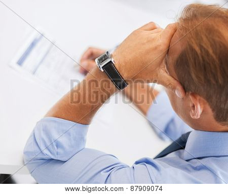business, office, school and education concept - stressed man filling tax form