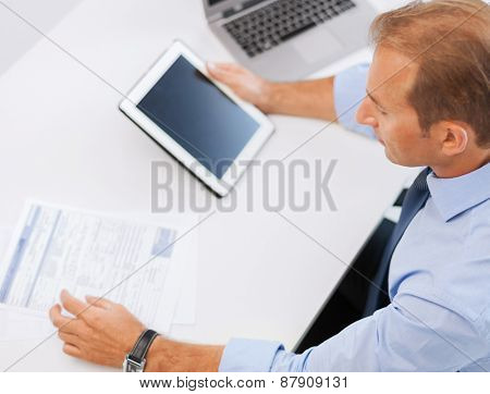 business, office, school and education concept - businessman with tablet pc and papers in office