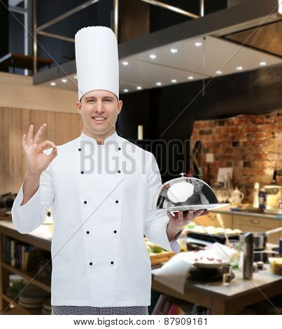 cooking, profession, gesture and people concept - happy male chef cook holding cloche and showing ok sign over restaurant kitchen