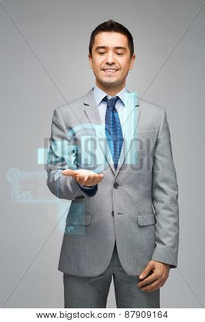 business, people, statistics and economics concept - happy businessman in suit showing or holding virtual chart projection on palm over gray background