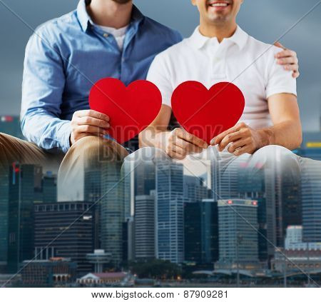 people, homosexuality, same-sex marriage, valentines day and love concept - close up of happy gay male couple with red hearts over city background