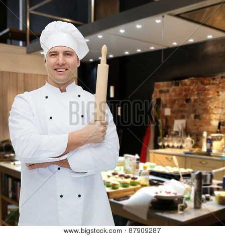 cooking, profession and people concept - happy male chef cook holding rolling pin over restaurant kitchen